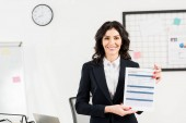 Fotografie attractive and cheerful recruiter holding resume in office