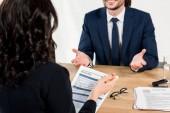 Fotografie selective focus of resume in hands of recruiter near man in office