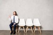 schöner Mann in formeller Kleidung sitzt auf einem Stuhl und gestikuliert, während er eine Idee hat