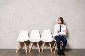 Fotografie schöner Mann sitzt mit verschränkten Armen auf Stuhl, während er auf ein Vorstellungsgespräch wartet
