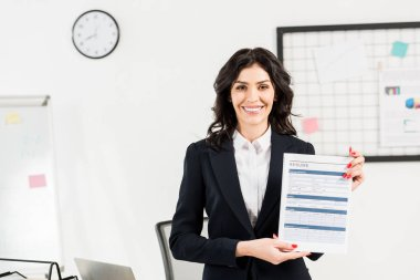 attractive and cheerful recruiter holding resume in office