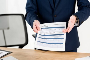 cropped view of recruiter holding resume while gesturing in office