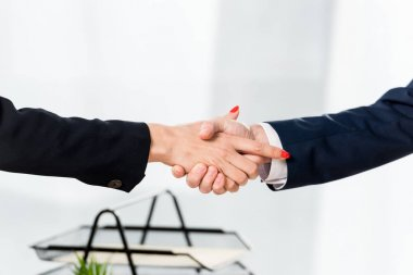 Cropped view of recruiter shaking hands with employee in office stock vector