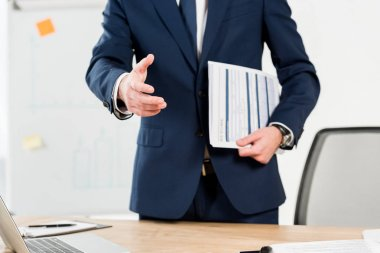 cropped view of recruiter holding resume and gesturing in office
