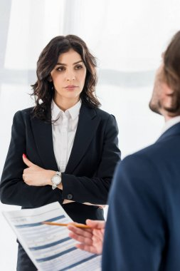 selective focus of attractive woman standing with crossed arms near man with resume