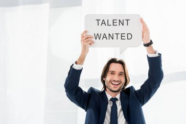 cheerful recruiter holding speech bubble with talent wanted lettering