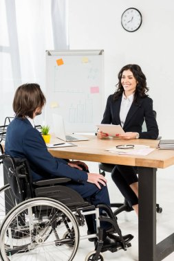 happy recruiter looking at disabled man while holding documents and smiling in office