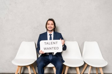 happy recruiter sitting on chair and holding speech bubble with talent wanted lettering