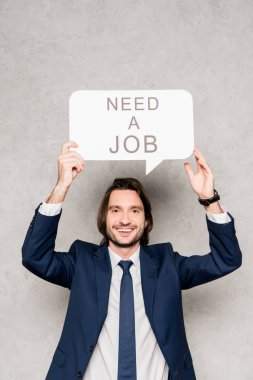 cheerful employee holding speech bubble with need a job lettering on grey