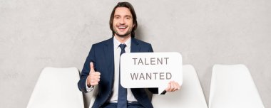 panoramic shot of happy recruiter sitting on chair and holding speech bubble with talent wanted lettering and showing thumb up