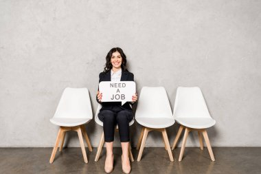 Happy brunette woman holding speech bubble with need a job lettering while sitting on chair stock vector
