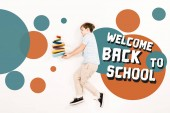 top view of child near colorful books and welcome back to school lettering on white