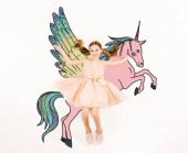Photo top view of cheerful kid looking at camera and gesturing near unicorn on white