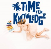 Fotografia top view of cheerful kid in pink dress holding books and flying near time for knowledge lettering on white