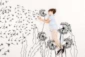 top view of kid blowing dandelion seeds while flying on white