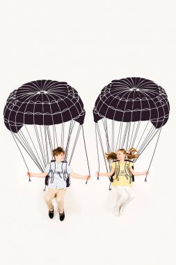 Top view of cheerful boy and happy girl holding parachutes while flying on white stock vector