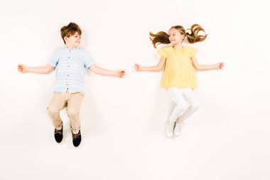 top view of cheerful kids looking at each other on white