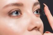 selektivní zaměření ženy připojení kontaktní čočky izolované na černém