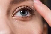 oříznutý pohled dívky připevňování kontaktní čočky izolované na černém