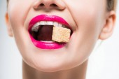cropped view of happy woman eating sugar cube on white