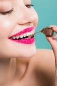 cropped view of cheerful woman eating chocolate candy isolated on blue