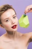 Fotografie attraktive nackte junge Frau hält Pappe grüne Birne isoliert auf lila