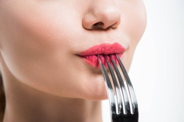 Cropped view of woman holding silver fork near pink lips isolated on white stock vector