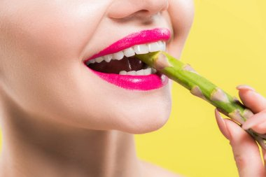 cropped view of cheerful woman holding green and tasty asparagus in mouth isolated on yellow