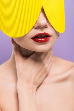 Young woman with red lips in yellow paper glasses touching neck isolated on purple stock vector