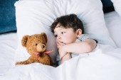 Fotografie cute kid lying on white pillow in bed and looking at teddy bear