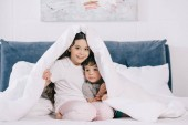 Fotografie cheerful kid sitting under blanket with cute toddler brother