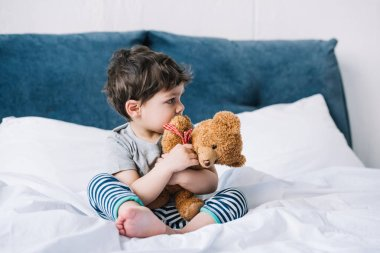 cute kid with barefoot sitting on bed and holding teddy bear