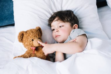 adorable kid lying on white pillow and touching teddy bear at home