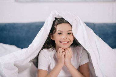 Happy kid smiling while sitting under blanket and looking at camera stock vector