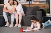 selektivní zaměření roztomilého kluka ležící na podlaze a kreslení na papír blízko šťastných rodičů