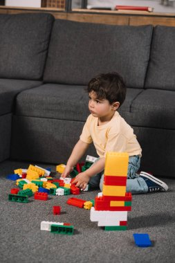 Selective focus of cute toddler playing with colorful toy blocks in living room stock vector