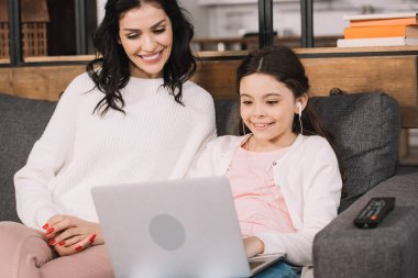 cheerful mother looking at laptop near daughter listening music in earphones