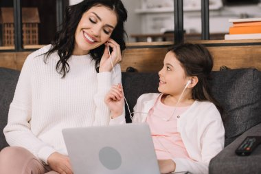 cheerful mother listening music in earphones near cute daughter with laptop