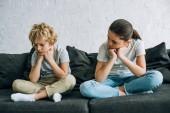 dva smutní děcka sedící na pohovce v obývacím pokoji