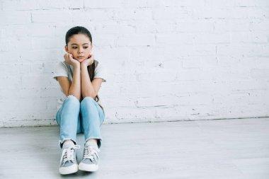 upset preteen child sitting on floor at home