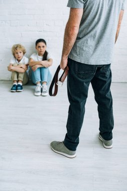 cropped view of abusive father holding belt and sad kids sitting on floor