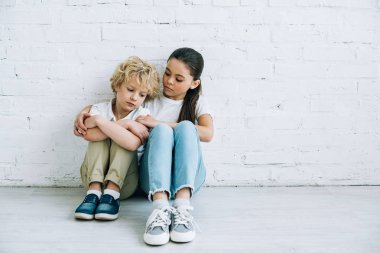 upset sister and brother sitting on floor at home