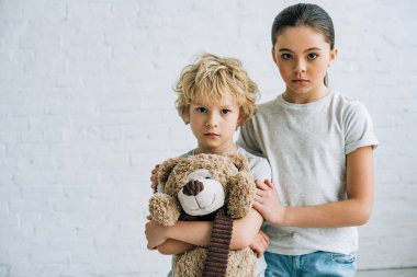sad sister and brother with teddy bear at home