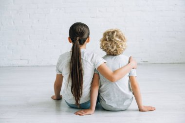 back view of two kids embracing on floor at home