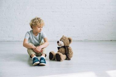 sad preteen boy with teddy bear sitting on floor