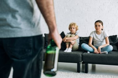 cropped view of alcohol addicted father with beer and upset children on sofa