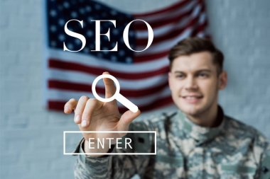 Selective focus of happy man in military uniform pointing with finger at seo lettering stock vector