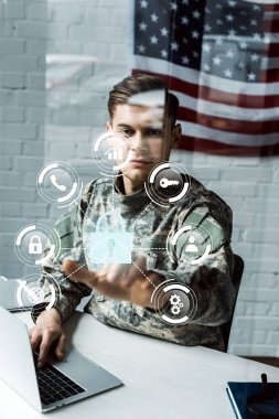 Handsome soldier in military uniform pointing with finger at virtual padlock while using laptop stock vector