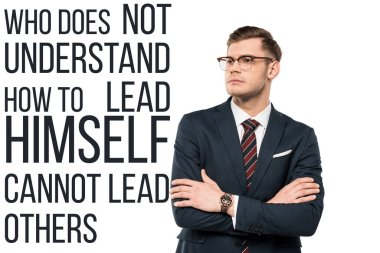 handsome businessman standing with crossed arms near who doesn't understand how to lead himself cannot lead others lettering on white