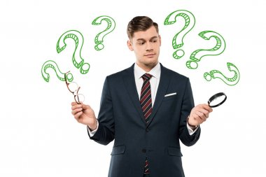 handsome businessman holding glasses and magnifying glass and question marks on white